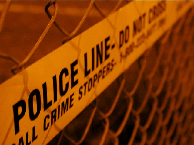 section of yellow police tape on chain link fence