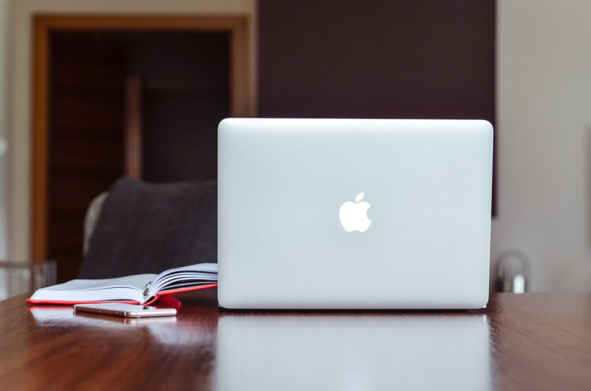 An open Apple laptop sitting on wood desk next to iphone and open book