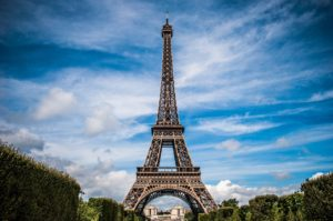 Eiffel Tower seen from a distance set against blue sky and clouds