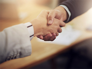 woman's arm and hand shaking man's hand wearing suite