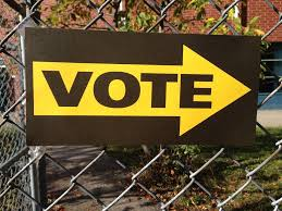 vote sign on fence outside of building